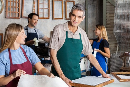 deckle: Portrait of smiling mature man making papers with colleagues in factory