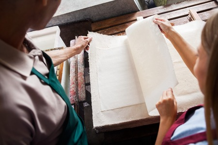 deckle: Male and female colleagues checking papers together in factory Stock Photo