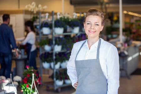 salesperson: Portrait of smiling mid adult female salesperson at flower shop Stock Photo