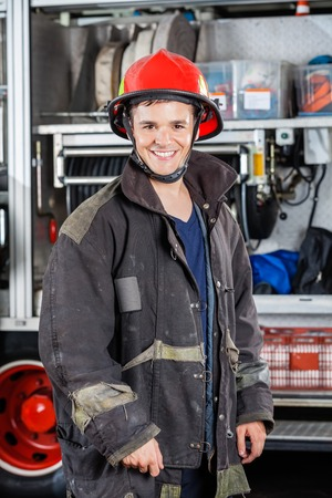 fireman: Portrait of happy young fireman standing against truck at fire station