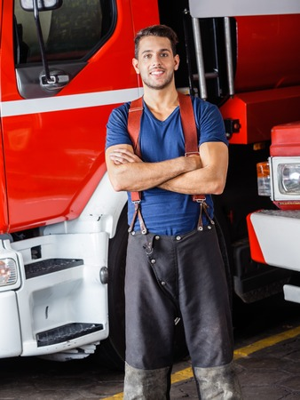 fire protection: Portrait of smiling young firefighter standing arms crossed against firetrucks at station