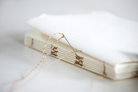 Closeup of needle and notepad papers on table
