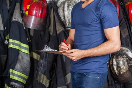 fire safety: Midsection of fireman writing on clipboard at fire station Stock Photo