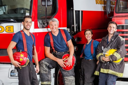 fire team: Team of happy firefighters leaning on trucks at fire station