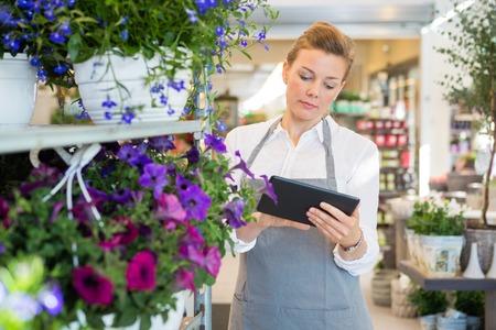 Medio volwassen vrouw met behulp van digitale tablet tijdens het staan door karretje in bloemenwinkel