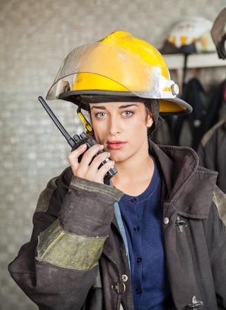 talkie: Portrait of confident firewoman using walkie talkie at fire station
