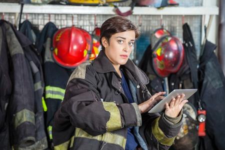 fireman: Portrait of confident firewoman in uniform using digital tablet at fire station
