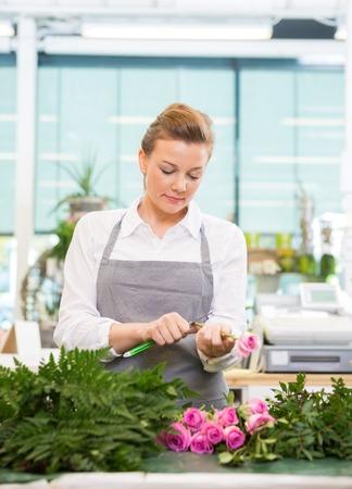 proprietor: Female florist cutting stem on pink rose at counter in flower shop