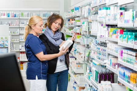 product: Female assistant showing product to woman holding cell phone in pharmacy