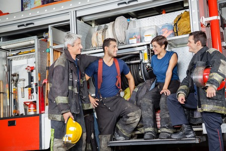 first responder: Team of male and female firefighters communicating by firetruck at station Stock Photo