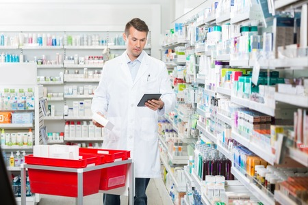 Mid adult male pharmacist updating stock in digital tablet at pharmacy