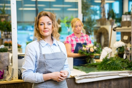ショップでバック グラウンドで動作の同僚と自信を持って女性花屋の肖像画 写真素材