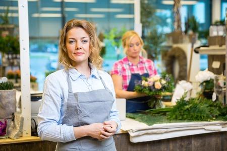 Portret van vertrouwen vrouwelijke bloemist met collega werken op de achtergrond in de winkel Stockfoto