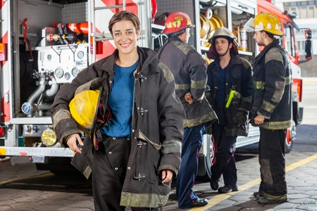 Portrait of happy firewoman with male colleagues discussing by truck in background at fire station Foto de archivo