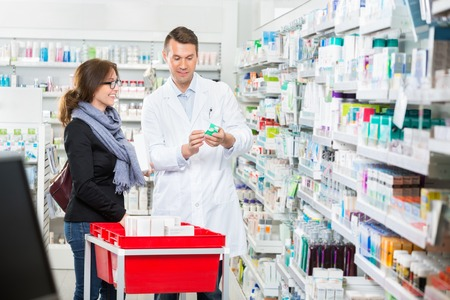 product: Smiling male pharmacist showing medicine to female customer in pharmacy