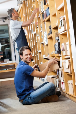 removing: Portrait of smiling male customer removing box from shelf with salesman working in background Stock Photo