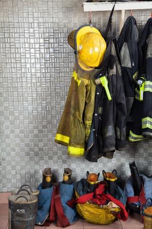 bombero: Trajes de bombero y equipos dispuestos en la estaci�n de bomberos