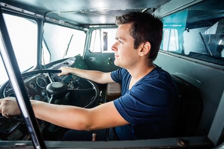 camion: Vista lateral de la joven bombero masculina de conducción de camiones en la estación de bomberos