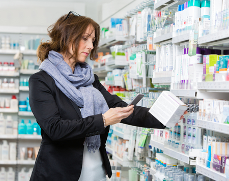 mid adult female: Mid adult female customer scanning product through mobile phone in pharmacy