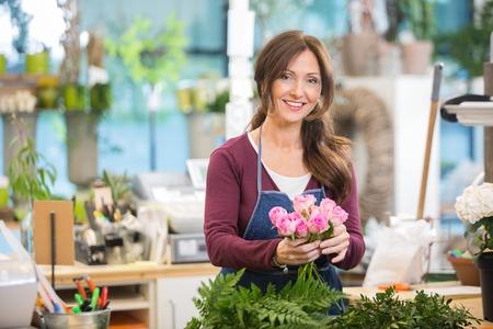 Portret van gelukkige bloemist die boeket roze rozen maakt in bloemenzaak