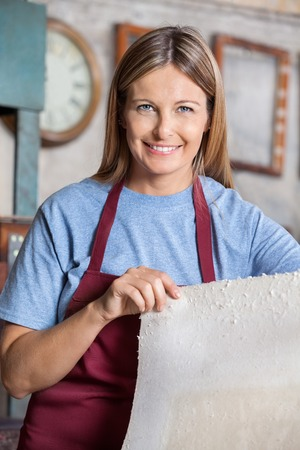 Portrait of confident female worker holding paper sheet in factory Stock Photo