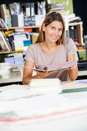 spiral book: Portrait of smiling mid adult female worker holding spiral book in factory