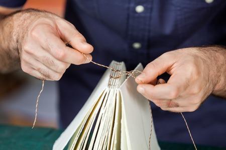 Buik van mannelijke werknemer bindende pagina's in papierfabriek Stockfoto