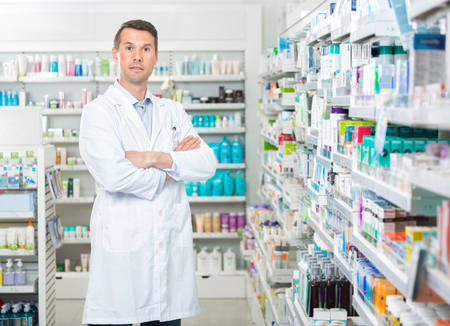 mid adult male: Portrait of confident mid adult male pharmacist standing arms crossed in pharmacy