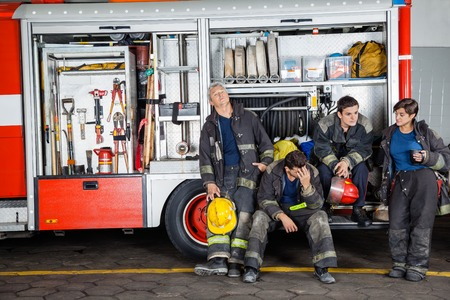 leaning on the truck: Team of exhausted male and female firefighters at truck in fire station