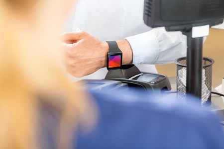 mobile: Midsection of male customer paying through smartwatch in pharmacy Stock Photo