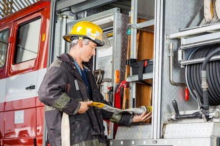 firefighter: Side view of male firefighter fixing water hose in truck at fire station Stock Photo