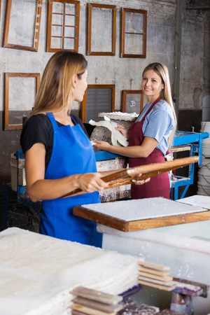 Female worker smiling while looking at coworker making papers in factory