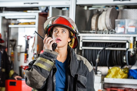 talkie: Confident female firefighter looking up while using walkie talkie at fire station