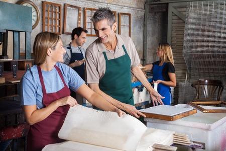empleados trabajando: trabajadoras que hacen los papeles masculinos y feliz mientras mira el uno al otro en la fábrica Foto de archivo