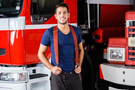 bombero: Retrato de la sonrisa bombero joven de pie contra camiones de bomberos en la estaci�n