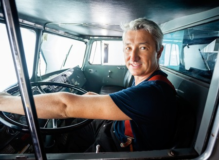 firefighting: Portrait of confident mature fireman driving firetruck at station Stock Photo