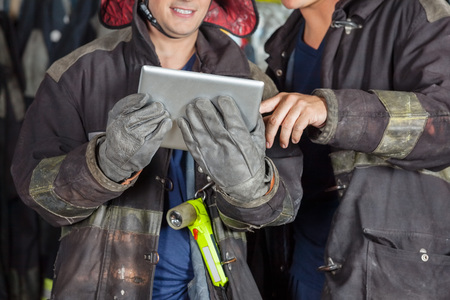 Midsection of male firefighters using digital tablet at fire station
