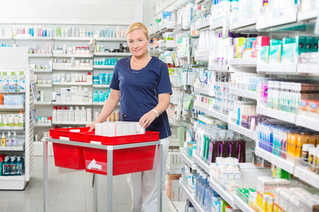 stockings woman: Portrait of smiling mature female chemist with products in baskets at pharmacy