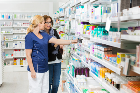 Female pharmacist removing product for customer from shelf in pharmacy Stockfoto