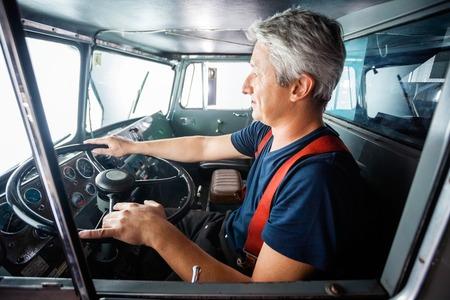 fireman: Side view of mature fireman driving firetruck at station
