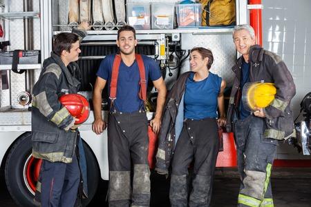 bombera: Equipo de bomberos confianza que se inclinan en camión en la estación de bomberos