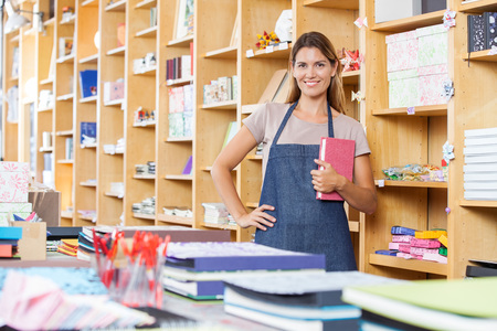 saleswoman: Portrait of confident saleswoman with hand on hip holding book in store Stock Photo