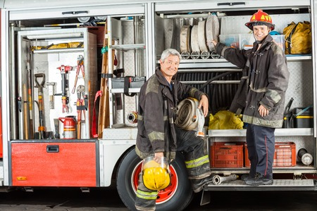 station: Portrait of confident male firefighters standing on truck at fire station