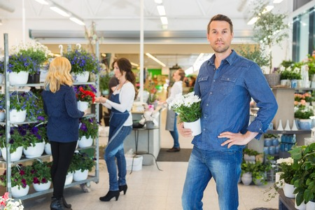 plant in pot: Portrait of confident man holding pot plant with florist assisting customer in background at shop