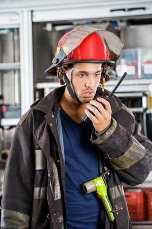 bombera: Bombero de sexo masculino joven que conversa en el walkie talkie en la estación de bomberos