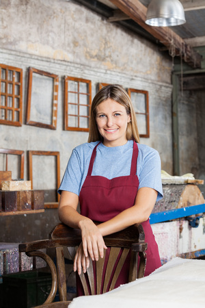 Portrait of confident female worker smiling while leaning on chair in paper factory