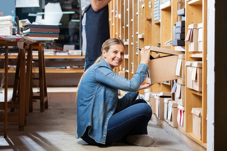 happy worker: Portrait of smiling female customer removing box from shelf with salesman working in background Stock Photo