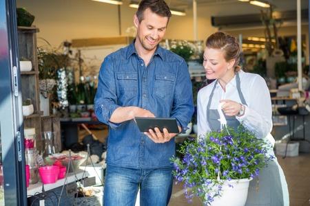 꽃집에 의해 서있는 동안 디지털 태블릿을 사용하는 남성 고객이 상점에서 식물 화분을 들고