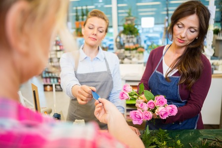 accepting: Florist accepting credit card from customer while colleague making rose bouquet at shop Stock Photo