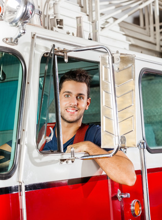 firetruck: Portrait of smiling young male firefighter sitting in firetruck